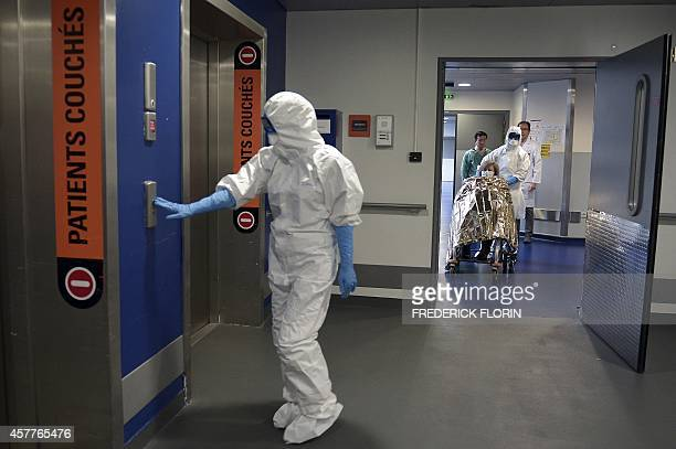 A member of the medical staff wearing protective suit presses a button to call the elevator as another pushes a woman sitting in a wheelchair and...