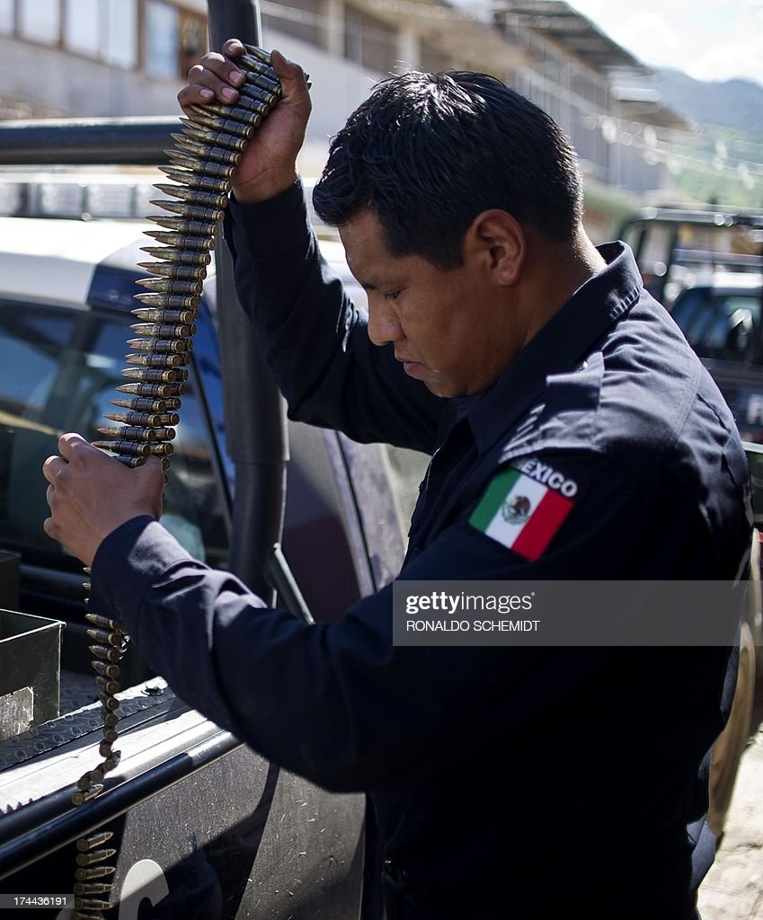 A member of the Mexican Federal Police counts bullets before a security operation in Aguililla, Michoacan state, Mexico on July 25, 2013. Gunmen attacked federal policemen in six villages of western Michoacan state and set up four roadblocks with a toll of 22 dead in the clashes, informed Tuesday the Ministry of Interior.