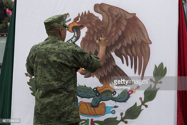 A member of the Mexican military paints the eagle of the Mexican national flag during Independence Day military parade at the Palacio Nacional in...