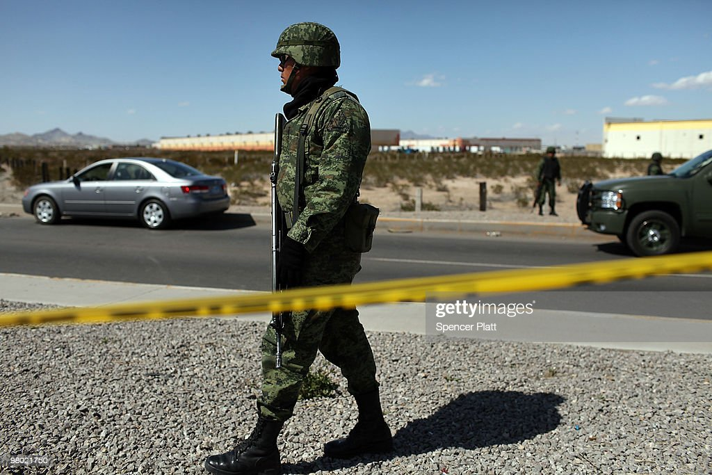 A member of the Mexican military police keeps guard over a car pictured at left bearing a bulletridden body on March 24 2010 in Juarez Mexico...