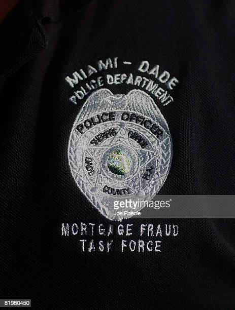 A member of the MiamiDade police Mortgage Fraud Task Force wears a shirt with their emblem during Operation 'Life is Good' July 17 2008 in Miami...