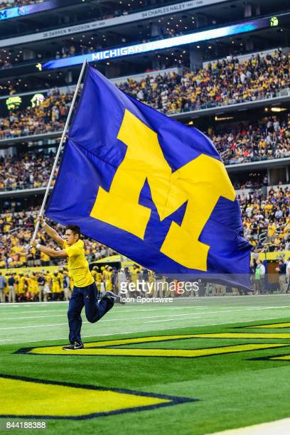 A member of the Michigan Wolverines flag squad sprints across the field after a touchdown during the game between the Michigan Wolverines and the...