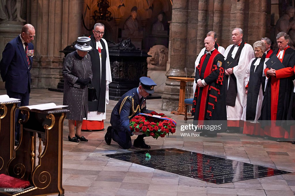 A member of the military lays a wreath made of roses and bay leaves on the Grave of the Unknown Warrior on behalf of Queen <a gi-track='captionPersonalityLinkClicked' href=/galleries/search?phrase=Elizabeth+II&family=editorial&specificpeople=67226 ng-click='$event.stopPropagation()'>Elizabeth II</a> (2nd L) and <a gi-track='captionPersonalityLinkClicked' href=/galleries/search?phrase=Prince+Philip&family=editorial&specificpeople=92394 ng-click='$event.stopPropagation()'>Prince Philip</a>, Duke of Edinburgh (L) at a Service on the Eve of the Centenary of the Battle of the Somme at Westminster Abbey on June 30, 2016 in London, United Kingdom.