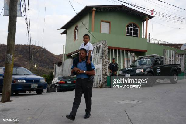 A member of the Military Police stands guard as a man takes his son to the Maximiliano Sagastume school in Sagastume a neighborhood on the north side...