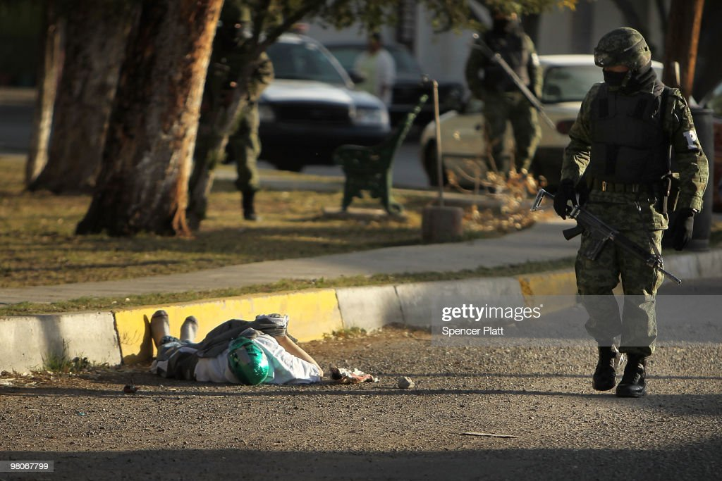 A member of the military police walks by a body with a mask in the street, one of numerous murders over a 24 hour period, on March 26, 2010 in Juarez, Mexico. Secretary of State Hillary Rodham Clinton, Defense Secretary Robert Gates, and Homeland Security Secretary Janet Napolitano all visited Mexico on March 23 for discussions centered on Mexico's endemic drug-related violence. The border city of Juarez, Mexico has been racked by violent drug related crime recently and has quickly become one of the most dangerous cities in the world to live. As drug cartels have been fighting over ever lucrative drug corridors along the United States border, the murder rate in Juarez has risen to 173 slayings for every 100,000 residents. President Felipe Calderon's strategy of sending 7000 troops to Juarez has not mitigated the situation. With a population of 1.3 million, 2,600 people died in drug-related violence last year and 500 so far this year, including two Americans recently who worked for the U.S. Consulate and were killed as they returned from a children's party.