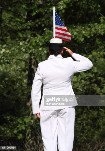 A member of the military replaces the flag pin and salutes on hole number sixteen during the third round of the Thornberry Creek LPGA Classic at...