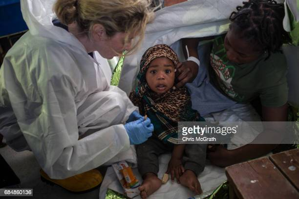 A member of the MOAS medical staff feeds a young baby on board the Migrant Offshore Aid Station Phoenix vessel after being rescued at sea on May 18...