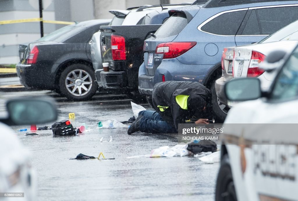 A member of the Montgomery County police searches for evidence under a car at the scene of a shooting in the parking lot of the Westfield Montgomery Mall in Bethesda, Maryland, on May 6, 2016 in which one person was killed and two others wounded. A federal police office was taken into custody Friday after shootings in suburban Washington shopping centers that left two people dead and two others wounded. Authorities said they had taken into custody Eulalio Tordil, a 62-year-old officer in the Department of Homeland Security's Federal Protective Service, which protects US government facilities. KAMM