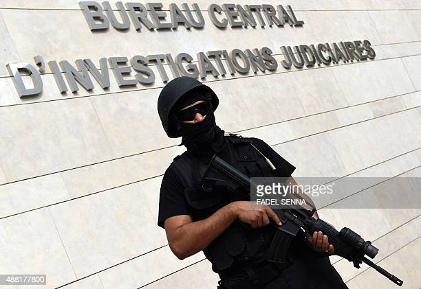A member of the Moroccan special forces stands guard outside the Moroccan Central Bureau of Judicial Investigation building during a press conference...