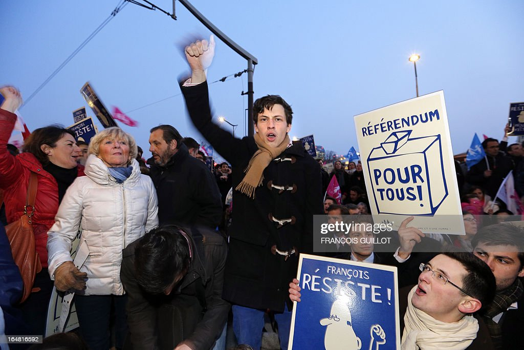 A member of the movement 'La Manif Pour Tous', opposed to same-sex marriage, holds up his fist in protest during a protest on March 28, 2013 outside the headquarters of France Television group in Paris, while the French president is interviewed during the broadcast news on the TV channel France 2. Placards read 'Francois, resist, prove that you exist!' and 'Referendum for all!'.