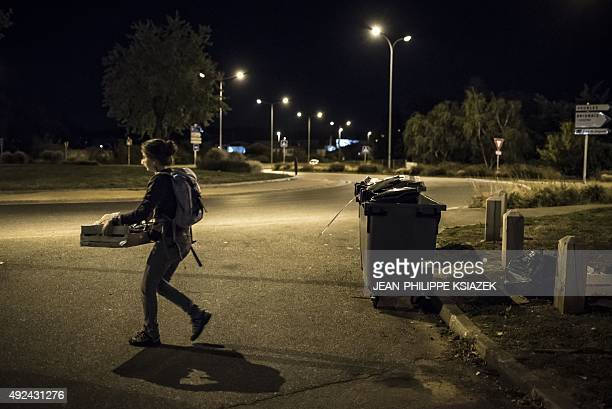 A member of the movement 'Les Gars'Pilleurs' carries a basket with food collect from waste containers of a supermarket in the south of Lyon France on...