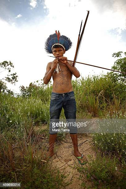 A member of the Munduruku indigenous tribe holds a bow and arrows along the Tapajos River during a 'Caravan of Resistance' protest by indigenous...