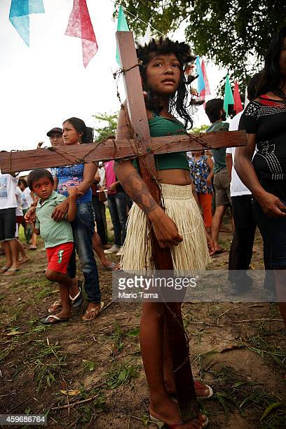 A member of the Munduruku indigenous tribe holds a cross along the Tapajos River during a 'Caravan of Resistance'' protest by indigenous groups and...