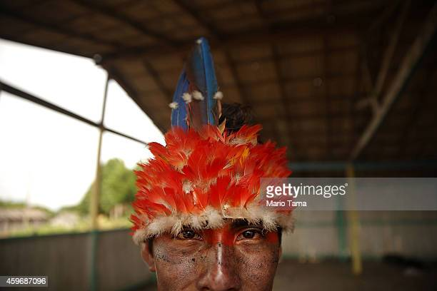 A member of the Munduruku indigenous tribe wears a traditional head dress near the Tapajos River in preparation for a 'Caravan of Resistance''...