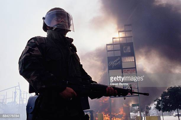 A member of the National Guard stands near burning building during the Los Angeles riots In April of 1992 after a jury acquitted the police officers...