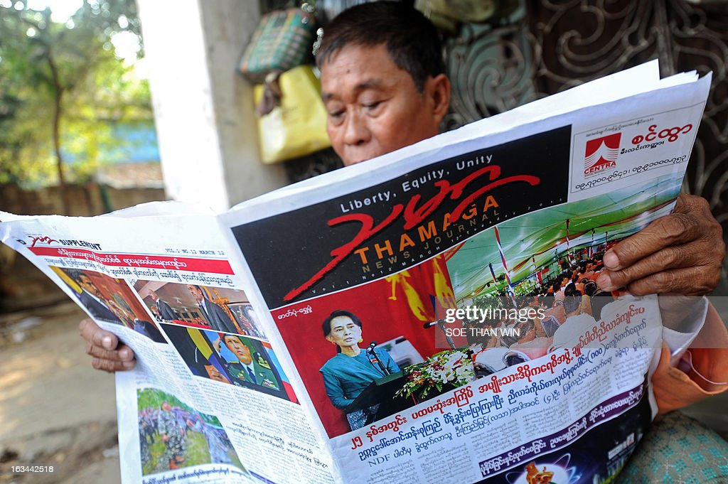 A member of the National League for Democracy (NLD) reads a local newspaper outside their party conference at the Royal Rose Hall in Yangon on March 10, 2013. Myanmar's long-silenced opposition reappointed Nobel laureate Aung San Suu Kyi as party leader at a landmark maiden congress, as it eyes victory in elections due in 2015. AFP PHOTO / Soe Than WIN