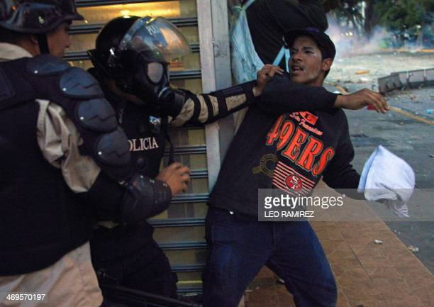 A member of the National Police struggles with an antigovernment student taking part in a protest in Caracas on February 15 2014 Supporters and...