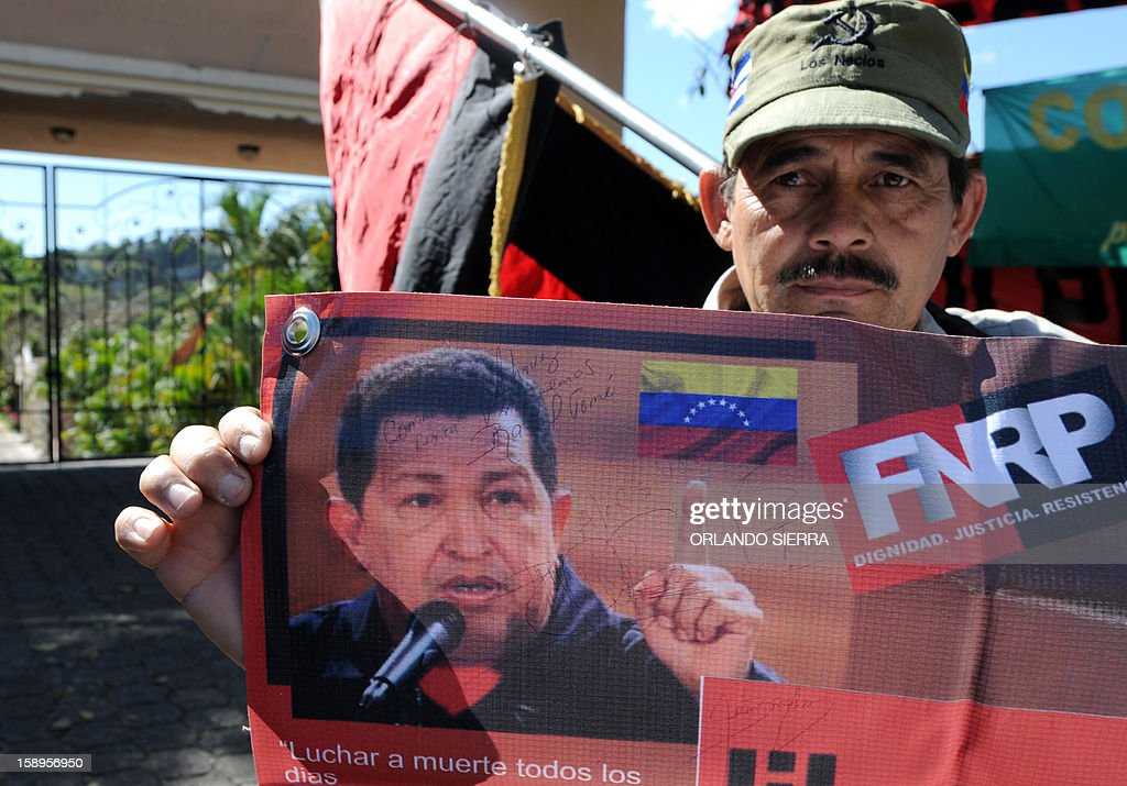 A member of the National Popular Resistance Front (FNRP), holds a poster of Venezuelan President Hugo Chavez, in Tegucigalpa, on January 4, 2013. Venezuelan Information Minister Ernesto Villegas said late January 3 that a 'severe pulmonary infection' that Chavez developed after his fourth round of cancer surgery in Cuba nearly a month ago had led to a 'respiratory insufficiency.' Chavez was re-elected October 7 despite his debilitating battle with cancer and the strongest opposition challenge yet to his 14-year rule in Venezuela. AFP PHOTO/Orlando SIERRA