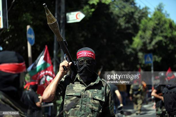 A member of the National Resistance Brigades the armed wing of the Democratic Front for the Liberation of Palestine holds an artillery during a march...