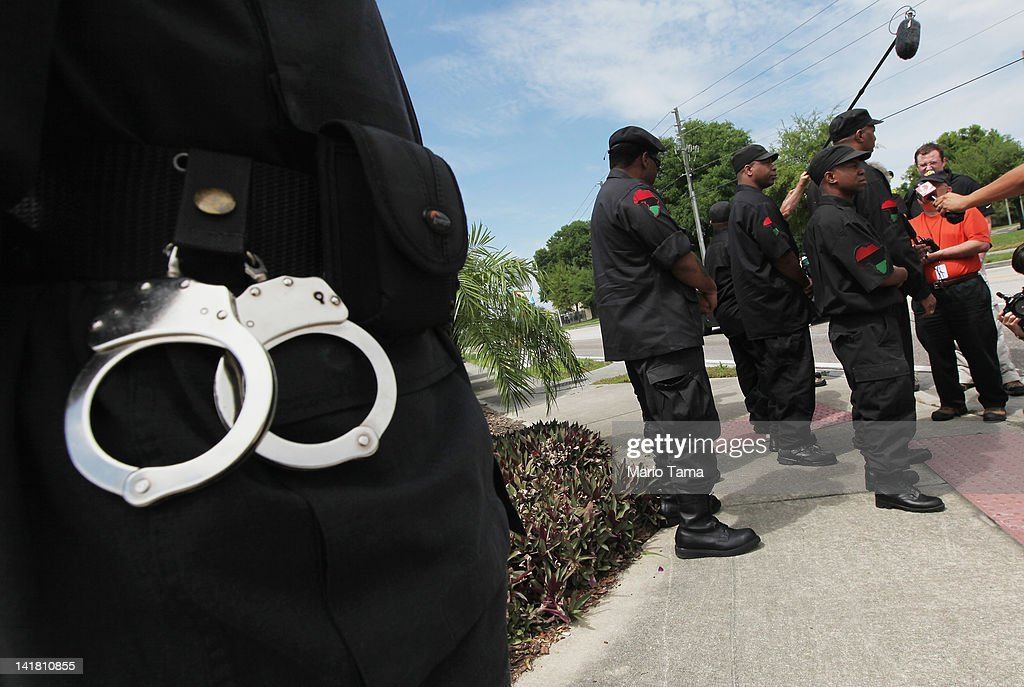 A member of the New Black Panther Party wears handcuffs as others rally next to a memorial to Trayvon Martin outside The Retreat at Twin Lakes...