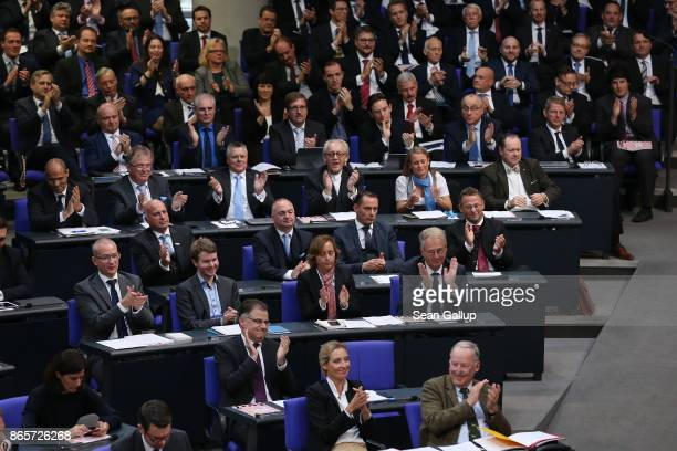Member of the new Bundestag faction of the rightwing Alternative for Germany applaude while attending the opening session of the new Bundestag on...