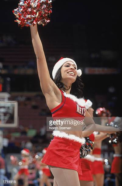 A member of the New Jersey Nets Power N' Motion Dance Team rallies the crowd during the Christmas day NBA game between the Boston Celtics and the New...