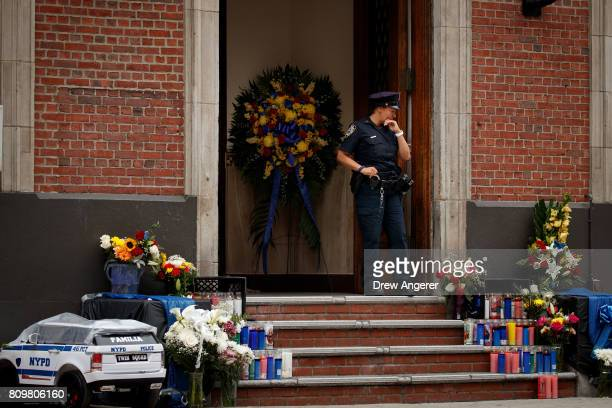 A member of the New York City Police Department stands at the entrance of the 46th Police Precinct near a makeshift memorial for fallen NYPD officer...