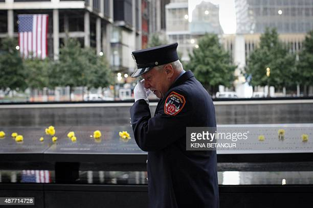 A member of the New York Fire Department reacts after he placed a flower on the 9/11 memorial before the ceremony to commemorate the 14th Anniversary...