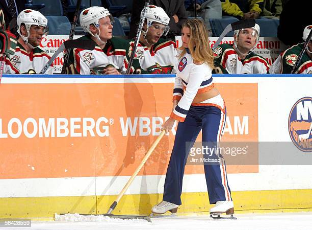 A member of the New York Islanders 'ice girls' cleans the ice in front of the Minnesota Wild bench during a timeout in their game on December 13 2005...