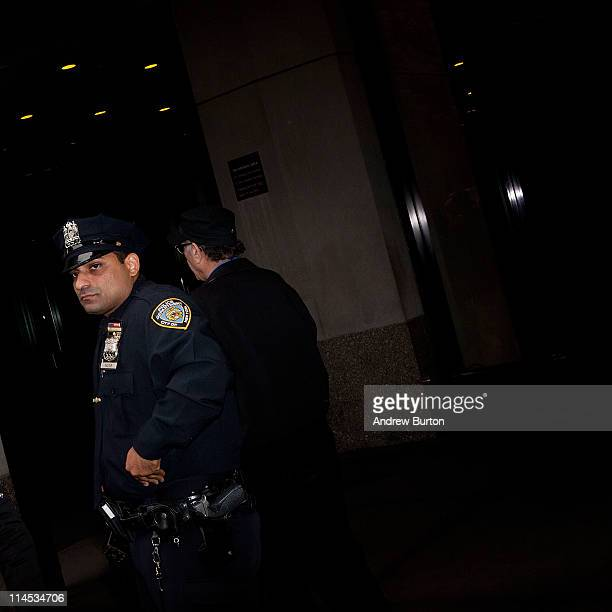 A member of the New York Police Department walks along the sidewalk across from 71 Broadway where Dominique StraussKahn is under house arrest on May...