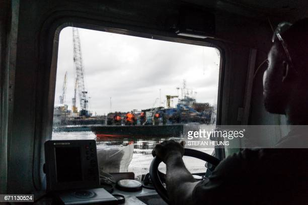 A member of the NNS Delta Of the Nigerian Navy forces steers a boat through the port area on April 19 2017 in the Niger Delta region near the city of...