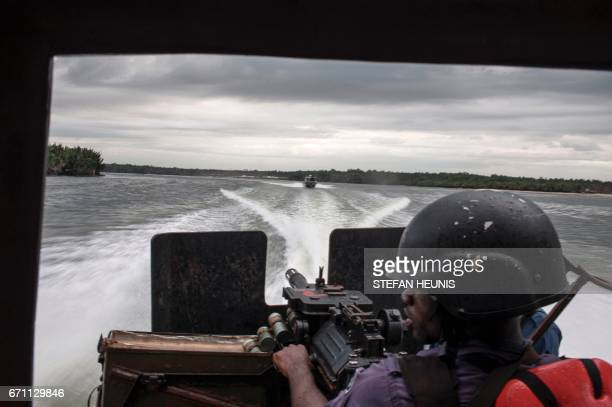 A member of the NNS Pathfinder of the Nigerian Navy forces surveys his surroundings from the back of a gunboat while on a patrol in the creeks...