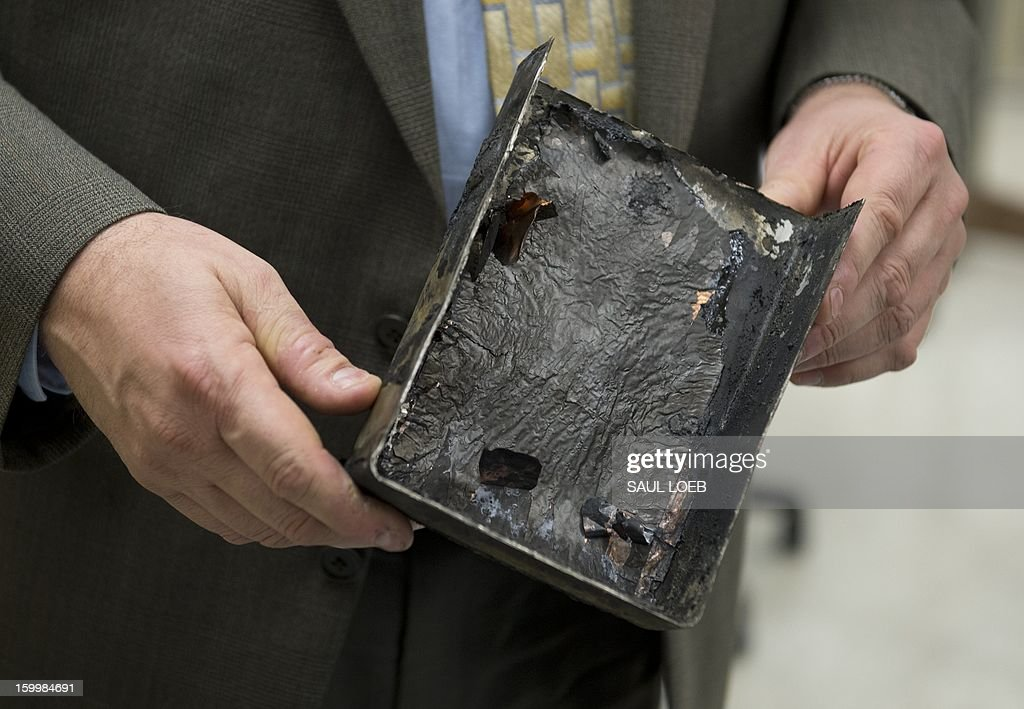 A member of the NTSB investigation team holds a damaged battery cell case from a fire aboard a Japan Airlines (JAL) Boeing 787 Dreamliner airplane at Logan International Airport in Boston earlier this month inside an investigation lab at National Transportation Safety Board (NTSB) Headquarters in Washington, DC, on January 24, 2013. The state-of-the-art composite aircraft continues to be grounded as the investigation into the cause of the thermal damage continues. AFP PHOTO / Saul LOEB