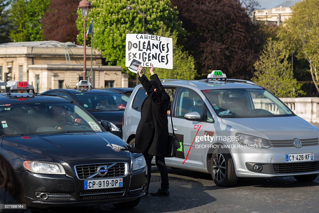 A member of the Nuit Debout movement hold a banner reading 'Registers of grievances and claims' as he protests against the controversial labour reforms in Paris, on May 3, 2016. About sixty Nuit Debout movement protesters stopped the traffic on Tuesday for several minutes on the Concorde bridge to raise members of parliament's awareness on their opposition to the controversial El-Khomri labour reforms a few hours before its vote at the Palais Bourbon. / AFP / Geoffroy Van der Hasselt