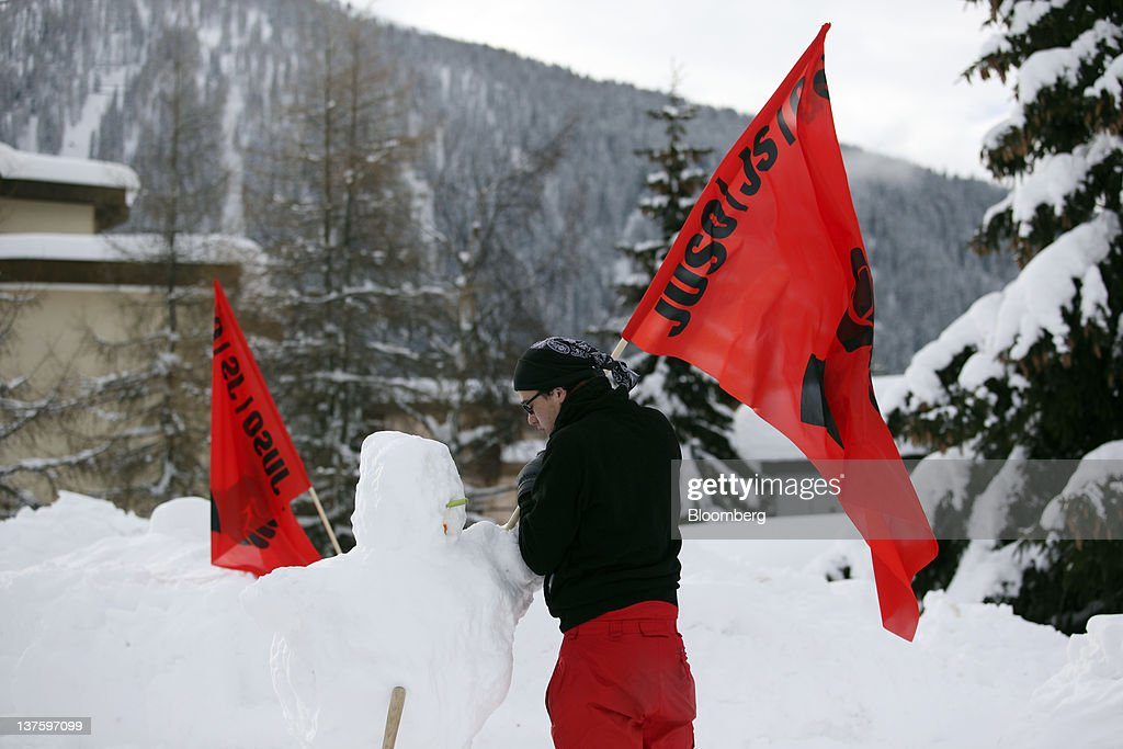 A member of the Occupy Davos protest group plants a protest flag in a snowman at their campsite in the centre of Davos, Switzerland, on Monday, Jan. 23, 2012. German Chancellor Angela Merkel will open this week's World Economic Forum in Davos, Switzerland, which will be attended by policy makers and business leaders including U.S. Treasury Secretary Timothy F. Geithner. Photographer: Chris Ratcliffe/Bloomberg via Getty Images