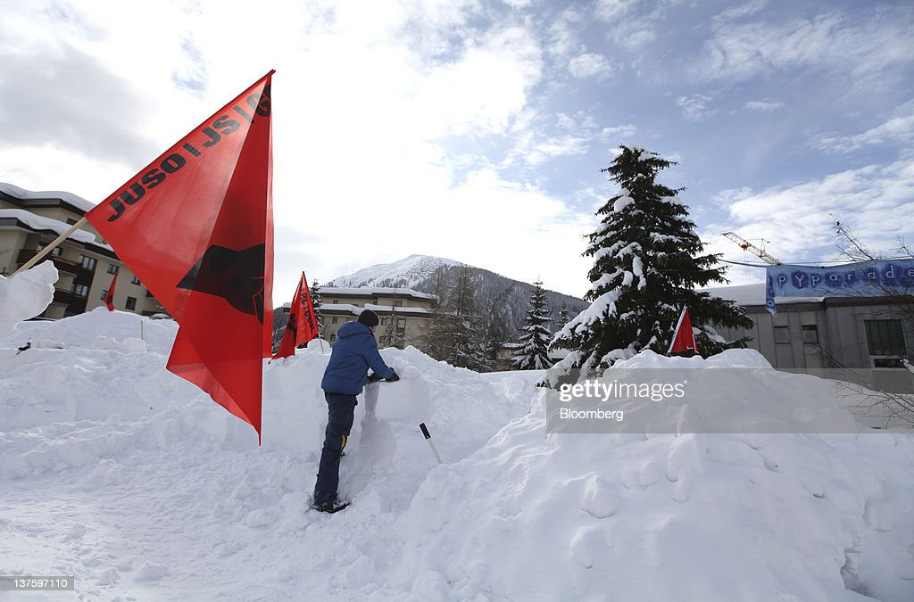 A member of the Occupy Davos protest group works on building an igloo at their campsite in the centre of Davos, Switzerland, on Monday, Jan. 23, 2012. German Chancellor Angela Merkel will open this week's World Economic Forum in Davos, Switzerland, which will be attended by policy makers and business leaders including U.S. Treasury Secretary Timothy F. Geithner. Photographer: Chris Ratcliffe/Bloomberg via Getty Images