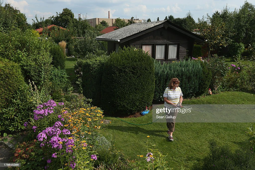 A member of the Oeynhausen Small Garden Association garden colony waters her lawn as the Reemtsma cigarette factory stands behind on August 29, 2013 in Berlin, Germany. At the Oeynhausen colony about 300 of its 438 gardens are currently threatened by real estate development, as are about another 24 colonies across the city. Berlin has about 900 garden colonies that are owned by the city and that provide urban dwellers who don't have land of their own the opportunity to maintain a garden and escape the stress of urban life. Berlin is currently undergoing a housing squeeze and city authorities are beginning to sell some of the colonies to developers, which has caused outrage in a city where the colonies of small gardens are a deep-seated tradition going back over a century.