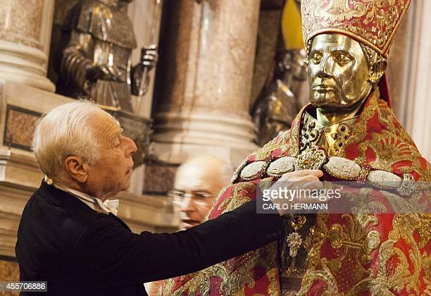 A member of the Order of Knights of San Gennaro that guard the ampoule containing the blood of the Saint prepare a statue during the celebrations of...