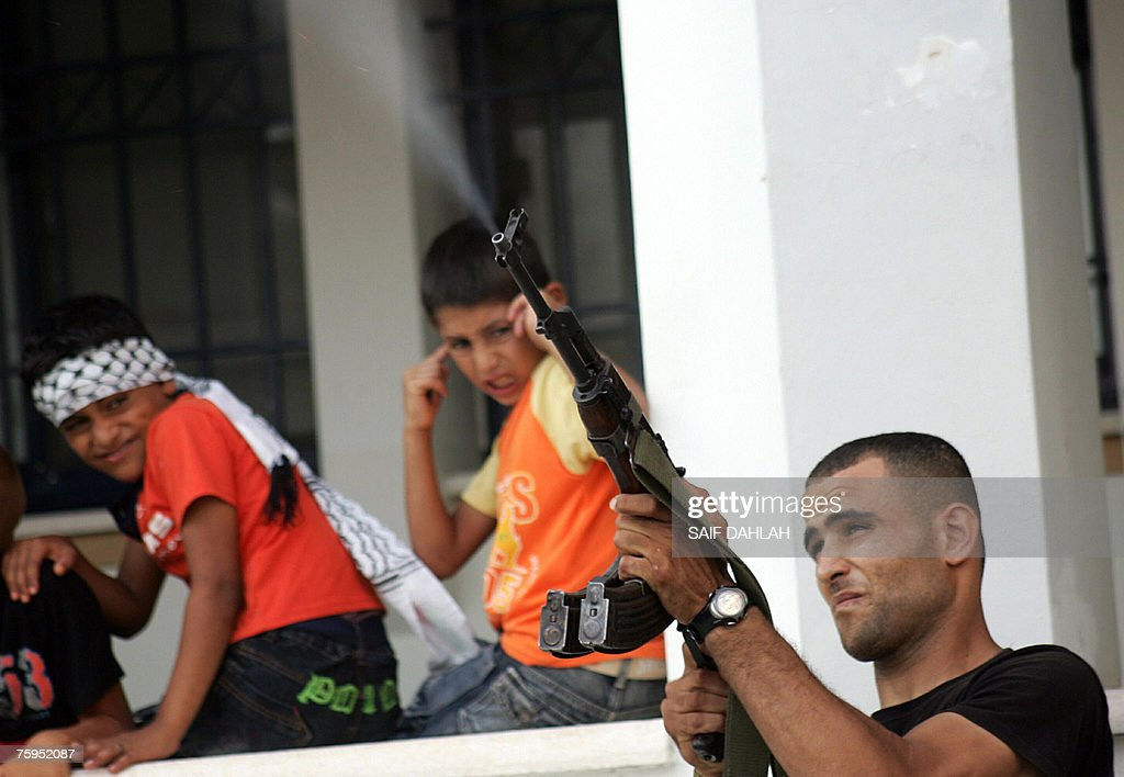 A member of the Palestinian Al-Aqsa Martyrs Brigades fires his weapon into the air as a young boy covers his ears in the background at a rally in the village of Kafr Dan, near the West Bank city of Jenin, 03 August 2007, in support of president Mahmud Abbas and the Palestinian government. Israeli troops have shot dead a leader of the radical Islamic Jihad group in the West Bank and wounded three people during an incursion into the Gaza Strip, Palestinian security sources and witnesses said today. AFP PHOTO/SAIF DAHLAH