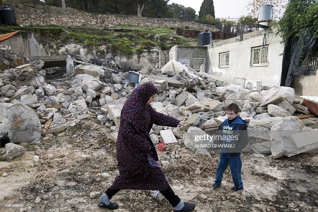 Member of the Palestinian Jabari family are seen close to the rubble of their house after it was demolished by Jerusalem municipality workers in the mostly Arab east Jerusalem neighborhood of Atur on December 11, 2012. Palestinian homes built without a construction permit are often demolished by order of the Jerusalem municipality.