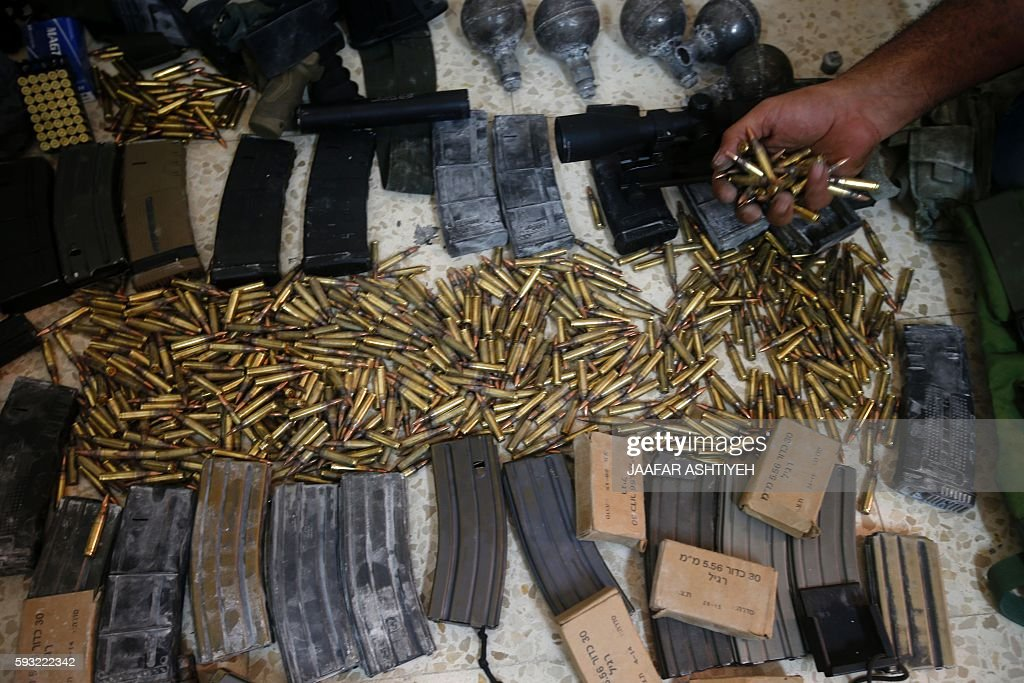 A member of the Palestinian security forces displays weapons at a police station in the West Bank city of Nablus that the police found on August 21...