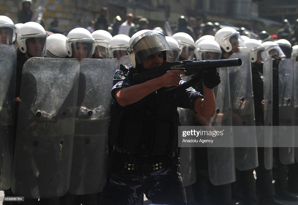 A member of the Palestinian security forces fires tear gas towards towards protestors after protestors set barricades on fire following a protest to show support for resistance movement Hamas in Hebron, West Bank on August 22, 2014.
