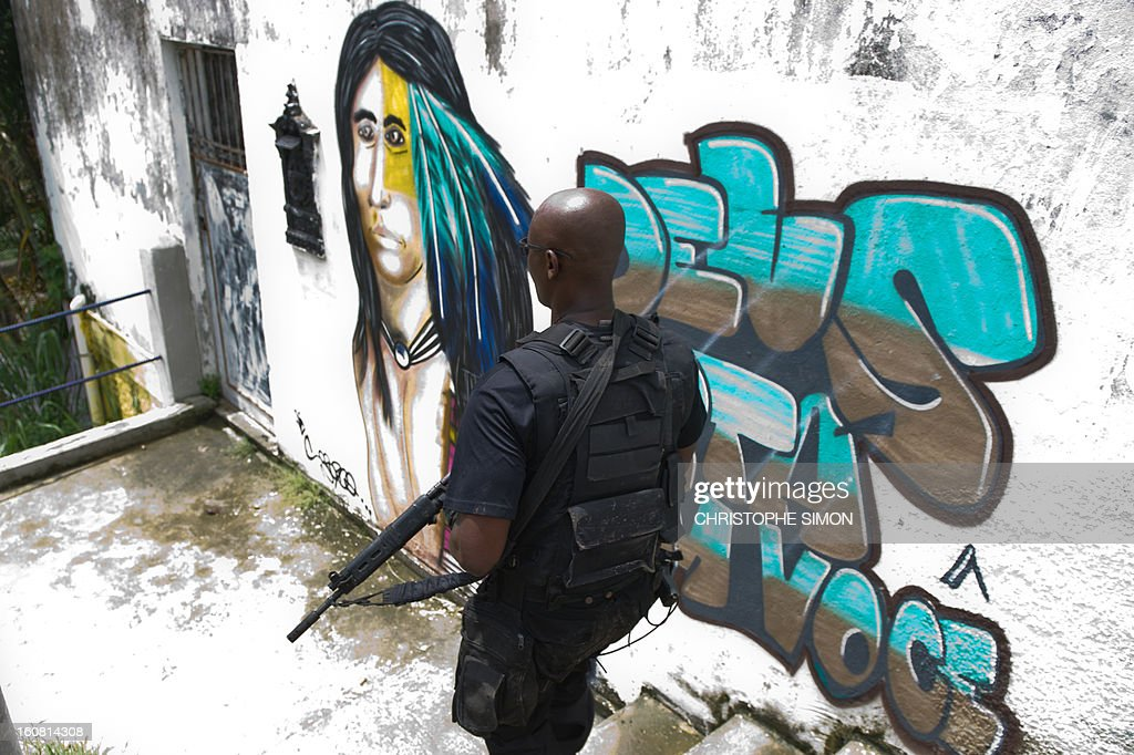 A member of the Paramilitary Police's elite unit BOPE patrols along an alley during an operation at Serrinha shantytown in Madureira, Rio de Janeiro, Brazil on February 6, 2013.