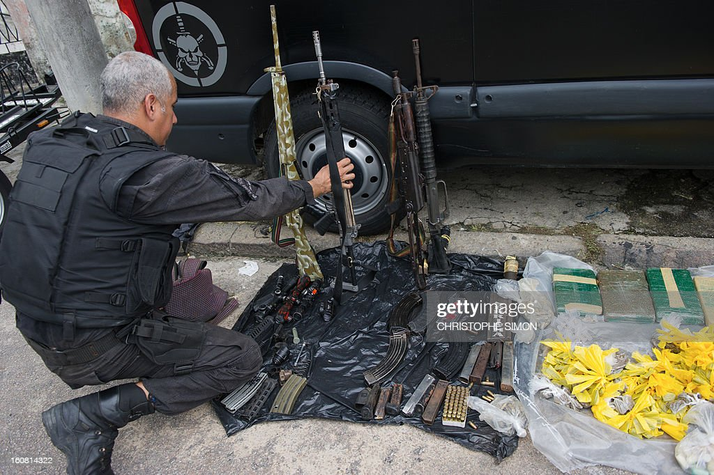 A member of the Paramilitary Police's elite unit BOPE shows assault rifles, ammo and drugs seized during an operation at Serrinha shantytown in Madureira, Rio de Janeiro, Brazil on February 6, 2013.