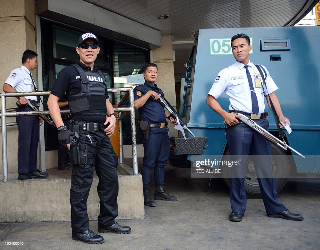 A member of the Pasay City SWAT team (L, in black) along with private security guards (R) stand guard next to an armored van in front of a bank in Manila on February 1, 2013, as part of heightened security and police visibility after recent attacks at shopping centres. Police have stepped up their visibility and security in response to recent attacks in popular Manila shopping malls, including the ransacking of a mall jewellery store on January 26.