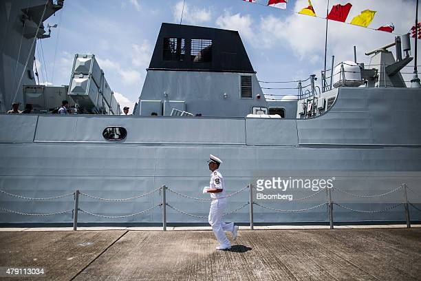 A member of the People's Liberation Army Navy runs past a ship during an open day at the Ngong Suen Chau Barracks in Hong Kong China on Wednesday...