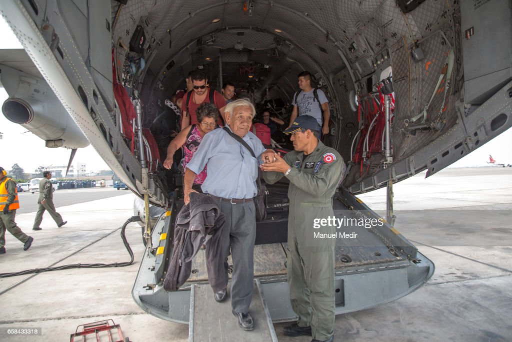 A member of the Peruvian Armed Forces helps an elderly man as he descends from the plain with flood victims from the North of Peru at Callao airport on March 27, 2017 in Callao, Peru. El Nino is causing severe storms since the begining of the rainy season in Peru now leaving more than 80 dead and at least 111,000 affected all over the territory.