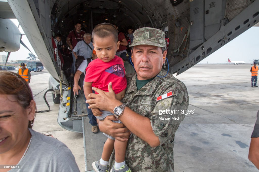 A member of the Peruvian Armed Forces holds a child as he descends from the C27-J Spartan plain with flood victims from the North of Peru at Callao airport on March 27, 2017 in Callao, Peru. El Nino is causing severe storms since the begining of the rainy season in Peru now leaving more than 80 dead and at least 111,000 affected all over the territory.