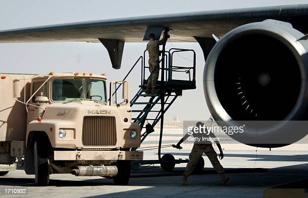 A member of the Petroleum Oils and Lubricants squadron at the 379th Air Expeditionary Wing supplies fuel to a KC10 aircraft on December 30 2002 in Al...