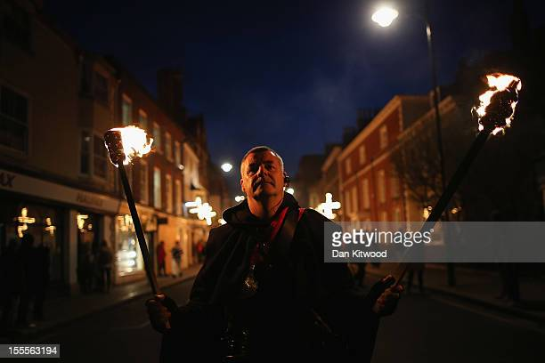 A member of the Pheonix Bonfre society walks with burning staffs during the Bonfire Night celebrations on November 5 2012 in Lewes Sussex in England...